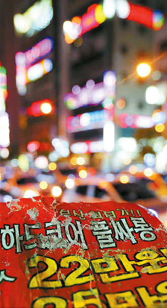 "Leaflets advertising ""full salon"" service were handed out to passersby at night on Dec. 2 in a red-light district in Busan. ""Full salon"" service implies a customer can drink with a hostess and then have sex for money in the same building. By Song Bong-geun"