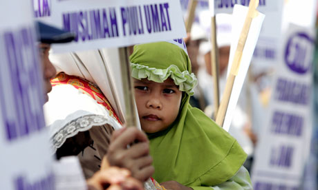 A girl rests in her mother's arms during a protest by Indonesian women against human trafficking and prostitution. Photograph: Darren Whiteside/Reuters