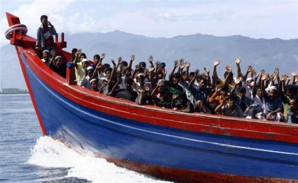 Ethnic Rohingya refugees from Myanmar wave as they are transported by a wooden boat to a temporary shelter in Krueng Raya in Aceh Besar, in this file picture taken April 8, 2013.  CREDIT: REUTERS/JUNAIDI HANAFIAH/FILES